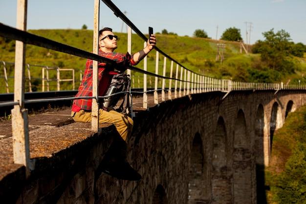 Man zit aan de rand van de brug en het nemen van selfie Gratis Foto