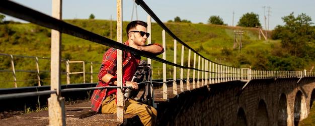 Man zit aan de rand van de brug Gratis Foto
