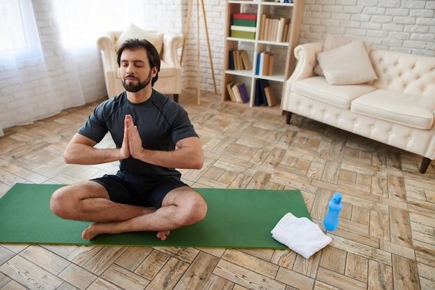 Man zit in de lotushouding op het groene tapijt. Premium Foto