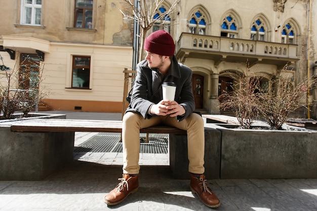 Man zit met een kopje koffie buiten in een zonnige dag Gratis Foto