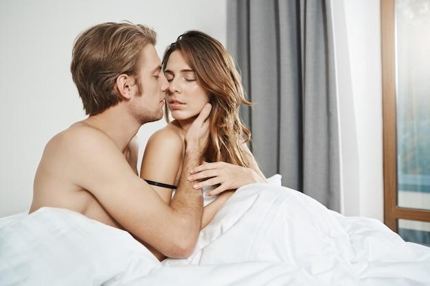 Man zit met zijn vrouw in bed, houdt haar hand op haar gezicht en kust terwijl haar ogen dichtgaan en haar hand zachtjes zijn arm aanraakt begin van sensueel ochtendvoorspel van pasgetrouwden. Gratis Foto
