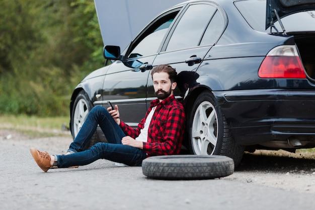 Man zittend op de weg en leunend op auto Gratis Foto