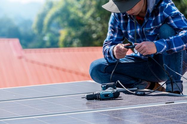 Man zonnepanelen installeren op een dakhuis voor alternatieve energie fotovoltaïsche veilige energie. Premium Foto
