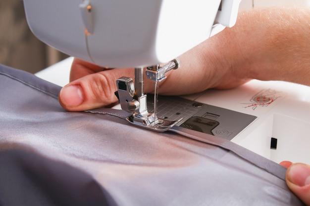 Man zoom een gordijn op een naaimachine. naaien, hobby's, hobby, huisverbetering. Premium Foto
