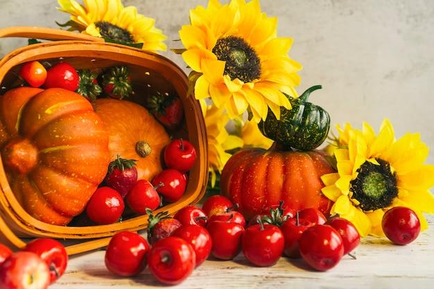 Mand met oogst dichtbij zonnebloemen Gratis Foto
