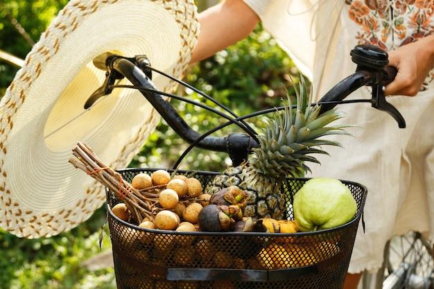 Mand op de fiets vol met verschillende exotische vruchten Premium Foto