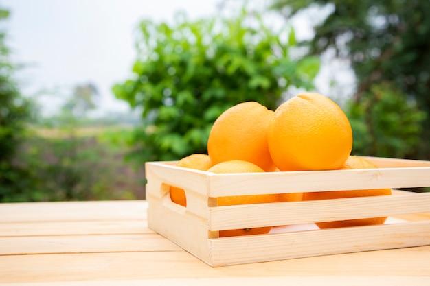 Mandarijn sinaasappelen geplaatst in een houten kist op de tafel. fruit is rijk aan vitamine c en helpt gezonde ogen te behouden en helpt staar voorkomen. Premium Foto