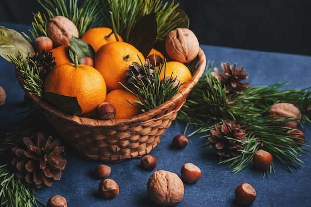 Mandarijnen, walnoten en hazelnoten versierd met dennenappels en takken Premium Foto
