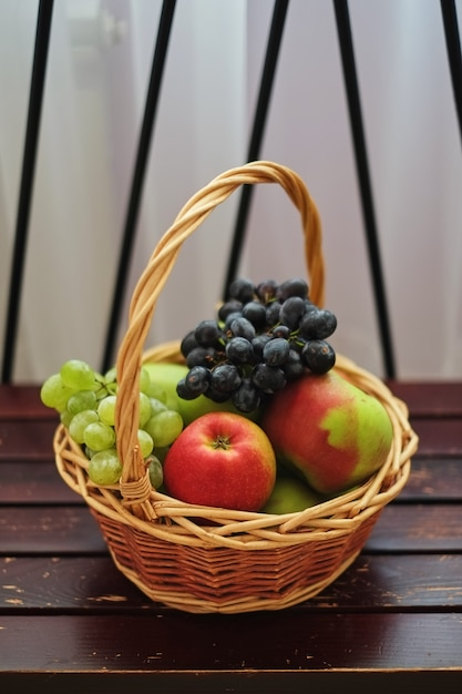 Manden met appels en rode en groene druiven. fruitmanden. Premium Foto