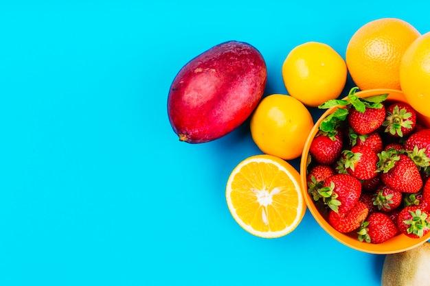 Mango; sinaasappelen en kom van aardbeien op blauwe achtergrond Gratis Foto