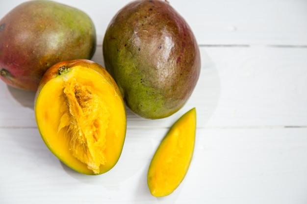 Mangovruchten close-up op witte houten achtergrond, Gratis Foto