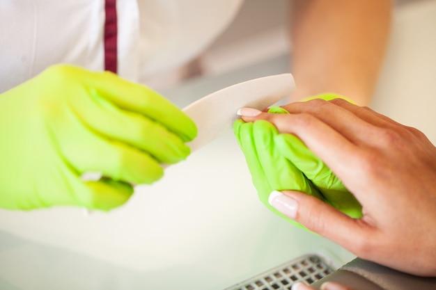 Manicure. bekwame meester van manicurebedrijfsdossier in haar handen terwijl het werken in haar schoonheidssalon Premium Foto