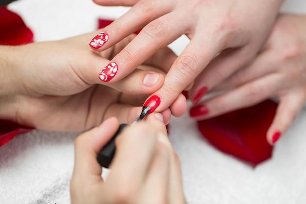 Manicure. de close-up van mooie vrouw overhandigt oppoetsende spijkers met rood nagellak in schoonheidssalon. close-up van de vrouwelijke cliëntspijkers van schoonheidsspecialisthand painting. schoonheid concept. hoge resolutie Premium Foto