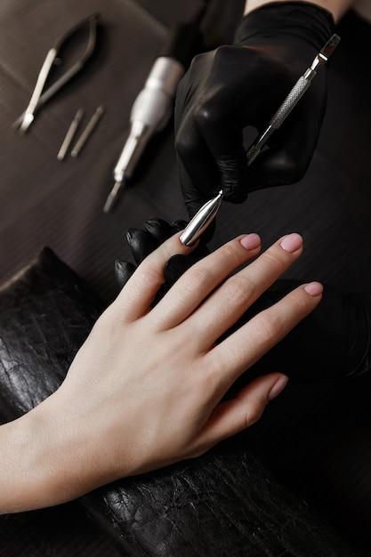 Manicure in zwarte handschoenen, pusher, bereidt nagels voor op procedures. nagel verlenging. spa faciliteiten. manicure kamer. Premium Foto