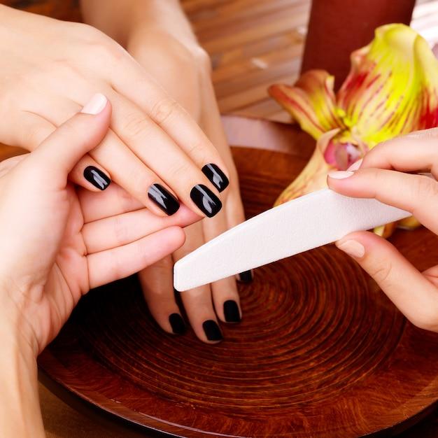 Manicure meester maakt manicure op handen van de vrouw - spa behandeling concept Gratis Foto