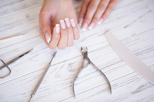 Manicure. sluit omhoog vrouwelijke handen situerend op bureau dichtbij spijkerhulpmiddelen Premium Foto
