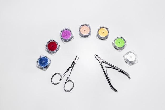 Manicureschaar en nagelknipper omringd door multi-gekleurde pailletten manicure Premium Foto