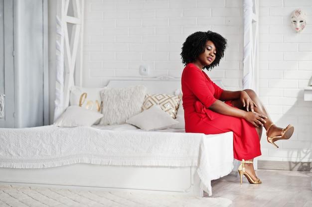 Manier afrikaans amerikaans model in rode schoonheidskleding, de sexy zitting van de vrouwen stellende avondjurk bij bed in witte uitstekende ruimte. Premium Foto