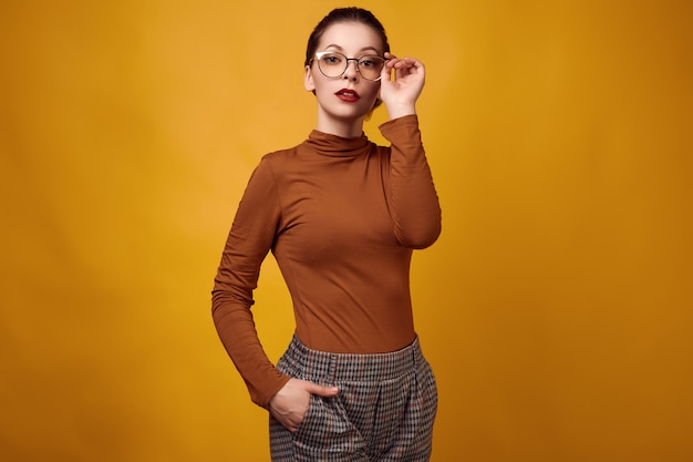 Manier donkerbruine vrouw die col en glazen op gele achtergrond dragen Premium Foto