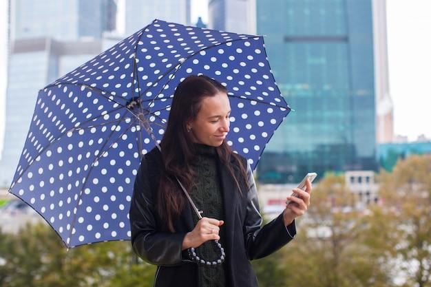 Manier jonge vrouw die op de telefoon met een in hand paraplu spreekt Premium Foto