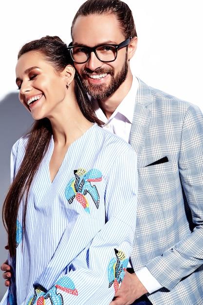 Manierfoto van de knappe elegante man in glazen in kostuum met mooie sexy vrouw in kleurrijke kleding op wit Gratis Foto