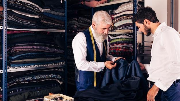 Manierontwerper die stof tonen aan zijn klant in de winkel Premium Foto