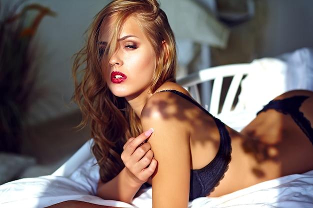Manierportret van mooi sexy jong volwassen blond vrouwenmodel die zwarte erotische lingerie dragen die op bed bij zonsondergang liggen Gratis Foto