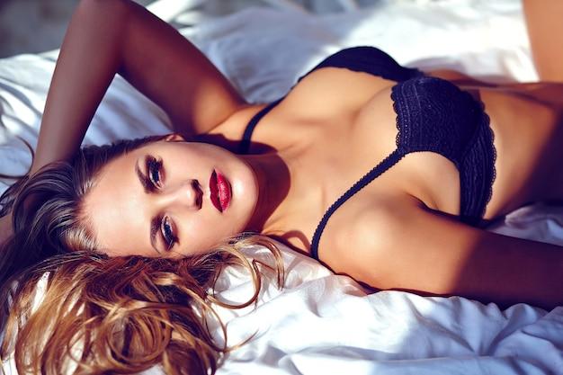Manierportret van mooie jonge vrouw die zwarte lingerie op wit bed dragen Gratis Foto