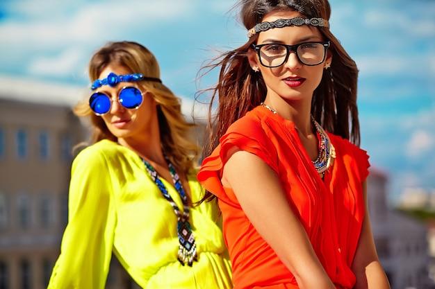 Manierportret van twee jonge modellen van hippievrouwen in de zomer zonnige dag in heldere kleurrijke hipsterkleren Gratis Foto
