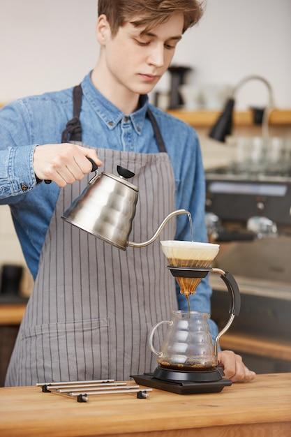 Mannelijk barista gietend water door gronden die pouronkoffie maken. Gratis Foto