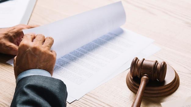 Mannelijke advocaat die de documenten in een rechtszaal op houten bureau draait Gratis Foto