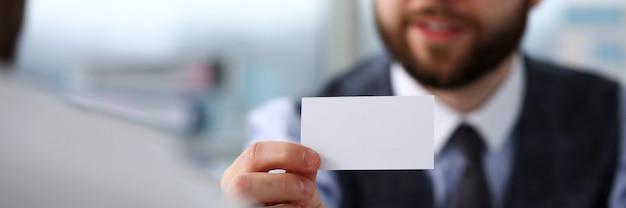 Mannelijke arm in pak geven blanco visitekaartje aan bezoeker Premium Foto