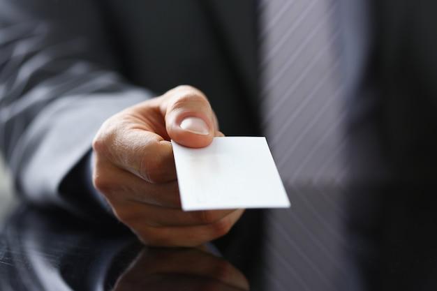 Mannelijke arm in pak geven blanco visitekaartje Premium Foto