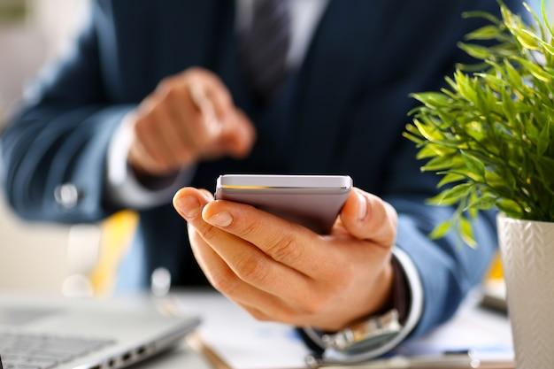 Mannelijke arm in pak houd telefoon Premium Foto