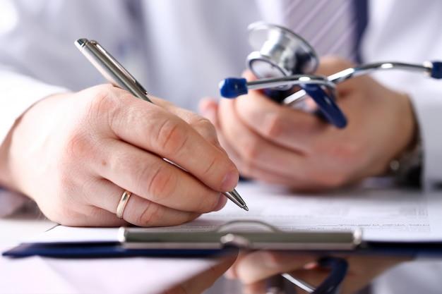 Mannelijke arts arm houden zilveren pen en pad Premium Foto