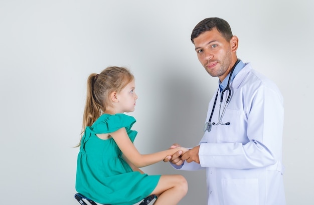 Mannelijke arts auscultating onderarm van kind in wit uniform in onderzoekskamer Gratis Foto