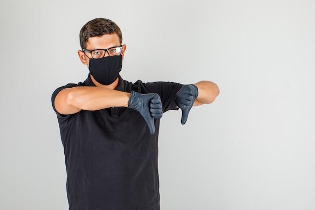 Mannelijke arts die duimen neer in zwart poloshirt tonen en ontevreden kijken Gratis Foto