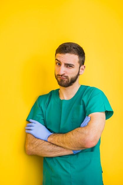 Mannelijke arts die met gekruiste wapens wenkbrauw opheft Gratis Foto