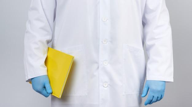 Mannelijke arts in een witte jas met knoppen met een gele papieren notitieblok Premium Foto
