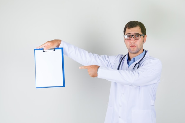 Mannelijke arts in witte jas, bril wijzende vinger op klembord Gratis Foto