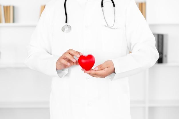 Mannelijke artsenhanden die pluchehart houden Gratis Foto