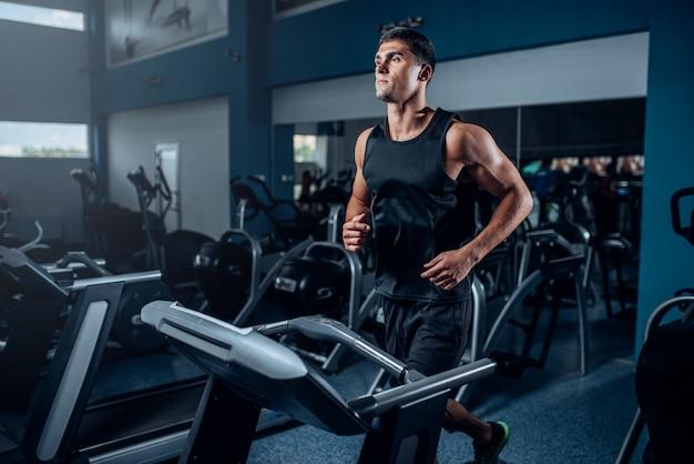Mannelijke atleet training op het runnen van oefeningsmachine. actieve sporttraining in de sportschool Premium Foto