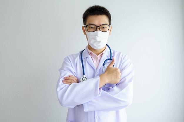 Mannelijke aziatische arts die in het kantoorziekenhuis werkt dat een gezichtsmasker draagt, beschermt covid 19-virussen. Premium Foto