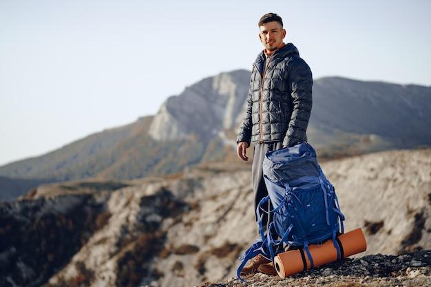 Mannelijke backpacker in wandeluitrusting die zich op de top van de berg bevindt Premium Foto