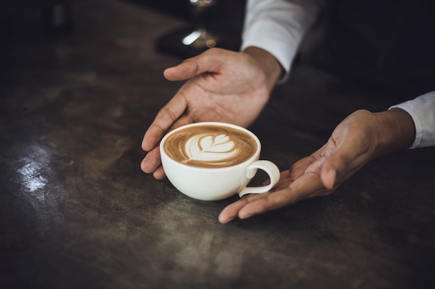 Mannelijke barista die koffie voor klant in koffiewinkel voorbereiden. cafe-eigenaar serveert een klant in de koffieshop. Premium Foto