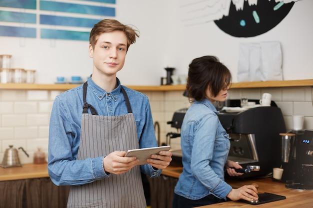 Mannelijke barista die orde neemt, die tab houdt, vrouwelijke barista die koffie maakt Gratis Foto