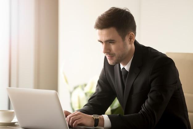 Mannelijke beambte die aan laptop in bureau werkt Gratis Foto
