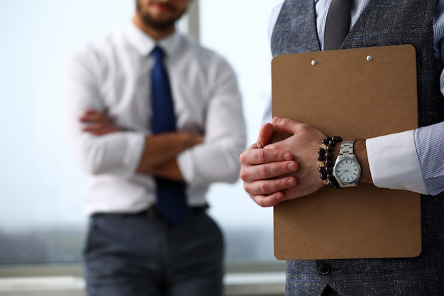 Mannelijke bediende arm in pak en stropdas met papier geknipt op pad Premium Foto