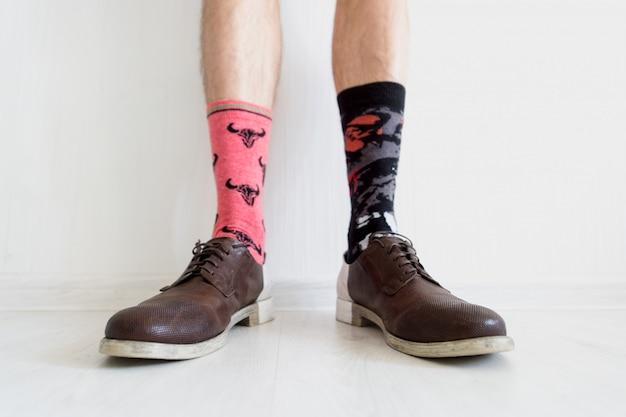 Mannelijke benen in niet-overeenkomende sokken die bruine schoenen over witte achtergrond dragen. Premium Foto