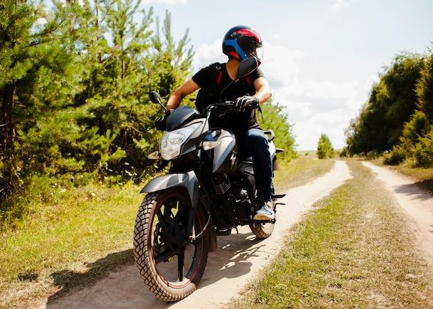 Mannelijke berijdende motor op landweg met helm Premium Foto